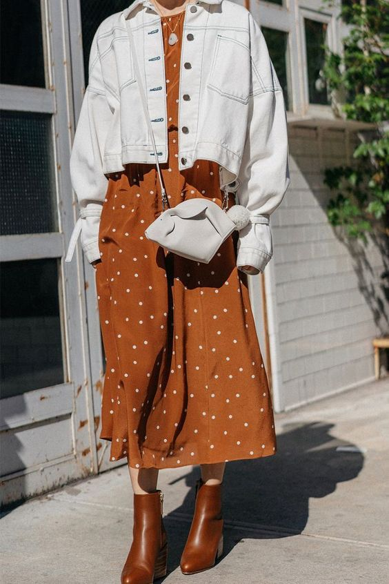 a rust and white polka dot midi dress, an oversized white denim jacket, rust colored booties and a white bag