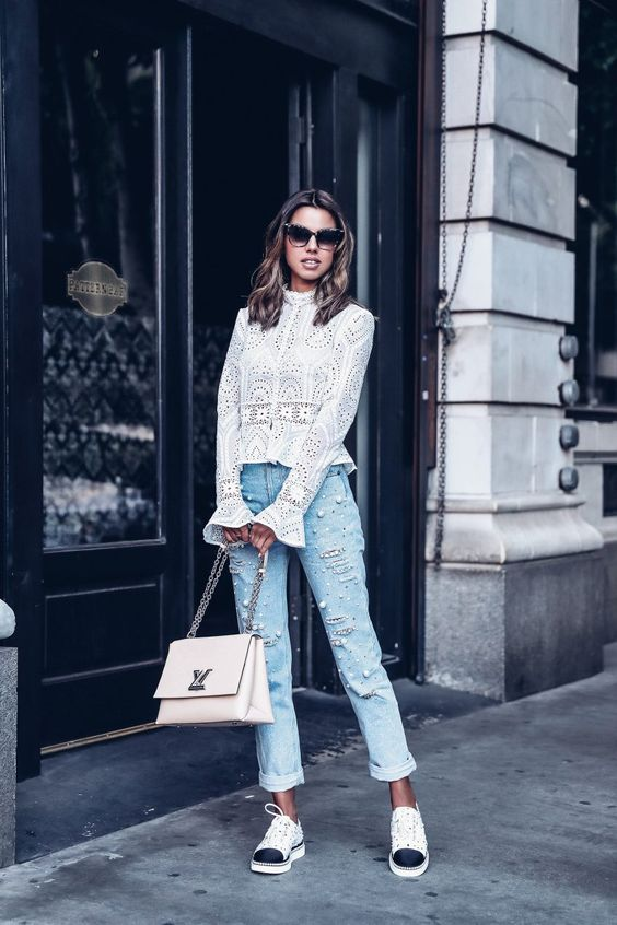 a white cotton lace blouse with bell sleeves and a turtleneck, pearl jeans, sneakers and a white bag