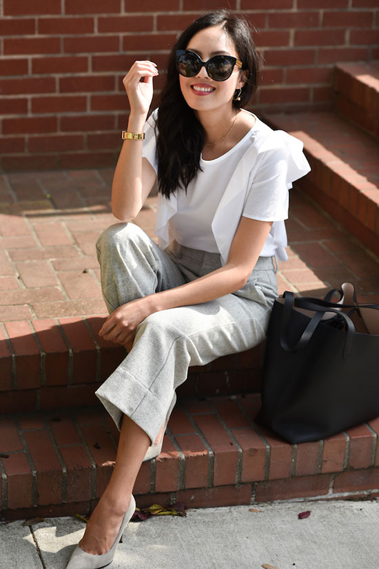 a white ruffled sleeve blouse, grey culottes and suede shoes plus a black tote for a cool summer look