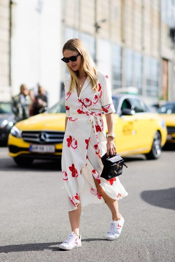 a neutral wrap dress with a bright floral print, white sneakers and a small black bag