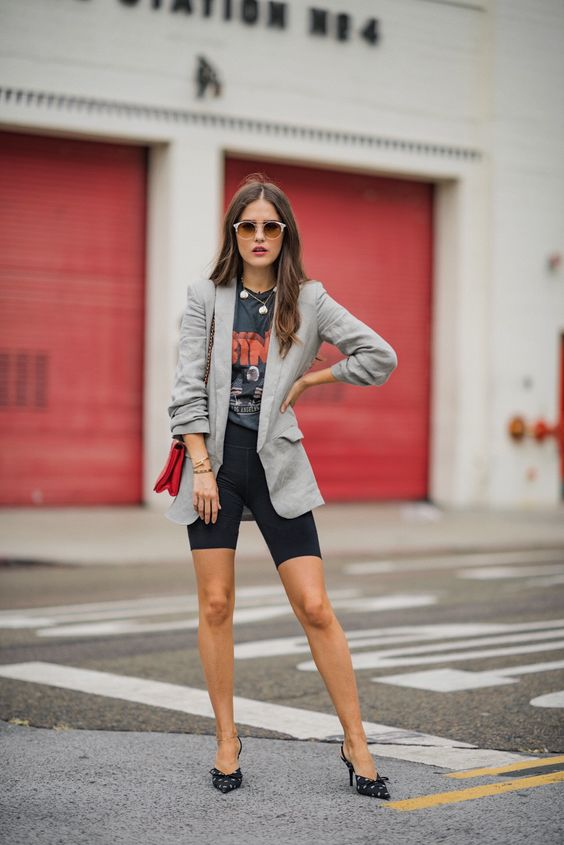 a printed tee, black bike shorts, polka dot slingbacks and a grey checked blazer plus a red bag