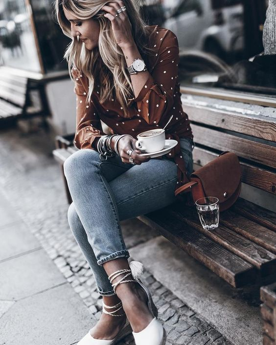 a rust and white polka dot shirt, blue skinnies, white espadrilles and a rust colored leather bag