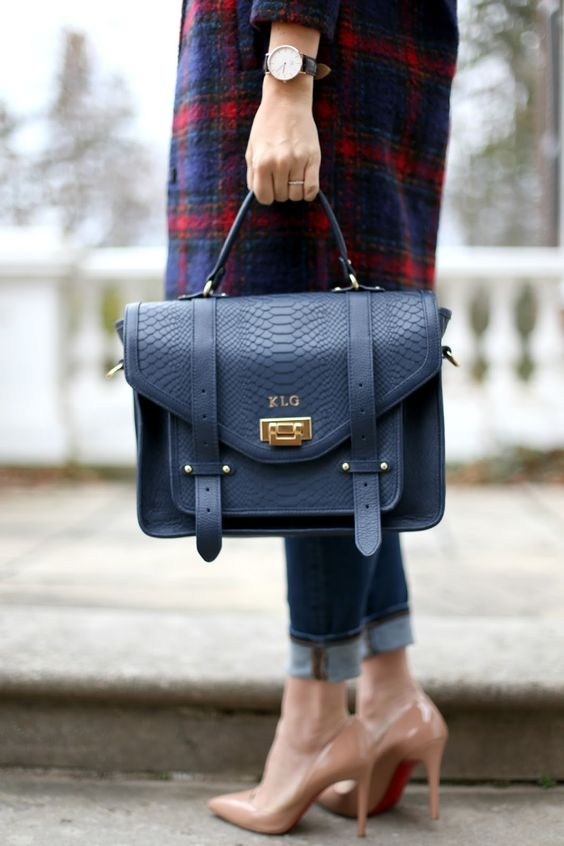 a structural navy leather bag with a snake texture and gold touches is a chic and bold idea