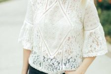 11 a white lace blouse with bell sleeves, black jeans and a brown bag for a stylish look
