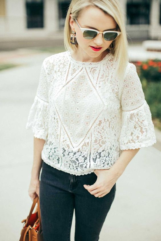 a white lace blouse with bell sleeves, black jeans and a brown bag for a stylish look