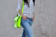 11 a white shirt, blue ripped denim, black pumps and a neon green bag as a bright accent