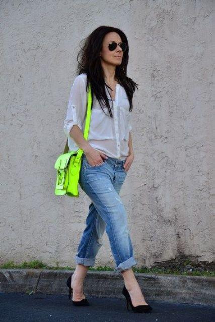 a white shirt, blue ripped denim, black pumps and a neon green bag as a bright accent