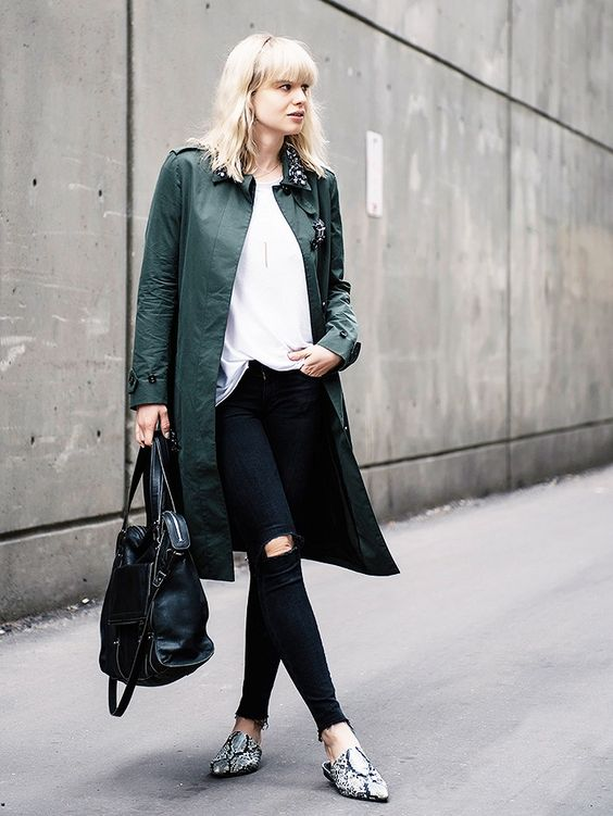 a white t-shirt is paired with an embellished olive green coat, distressed skinny jeans, snakeskin mules, and a black bag