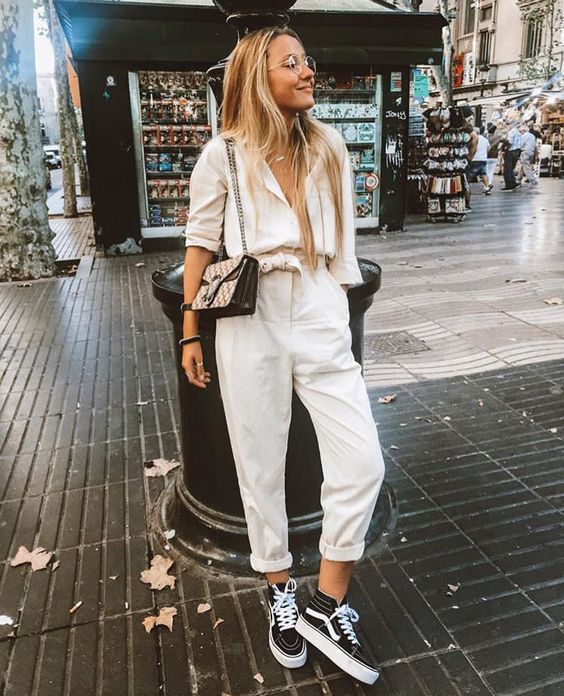 an off white jumpsuit with a cargo feel, black Vans snakers and a small bag
