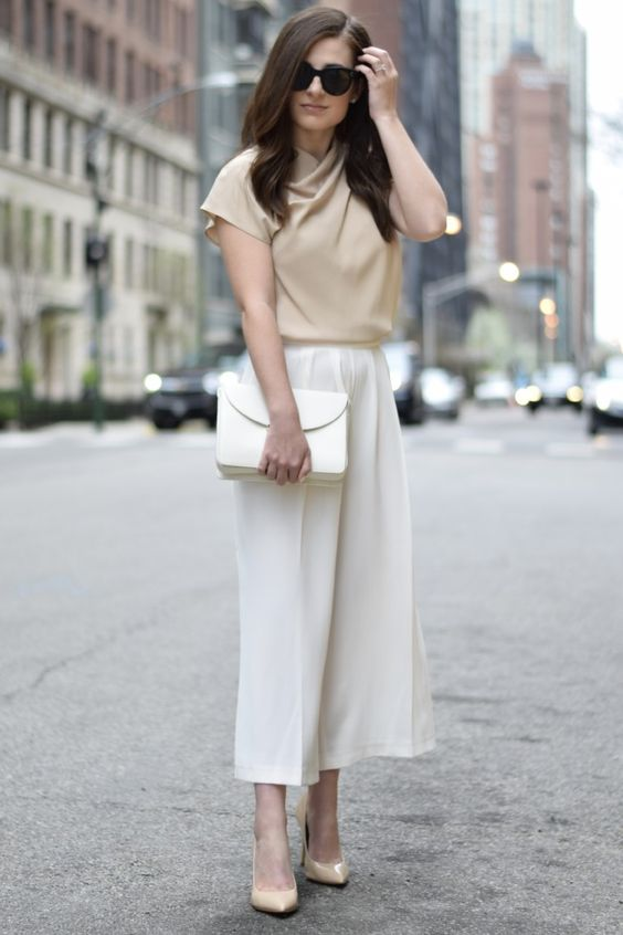 white culottes, a tan top with short sleeves, nude shoes and a white clutch make up a very comfy look