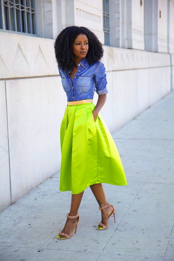 a chambray shirt, a neon green A line midi skirt, nude and neon heeled sandals