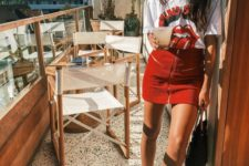12 a graphic oversized tee, a red mini with a zip, white sneakers and a black bag