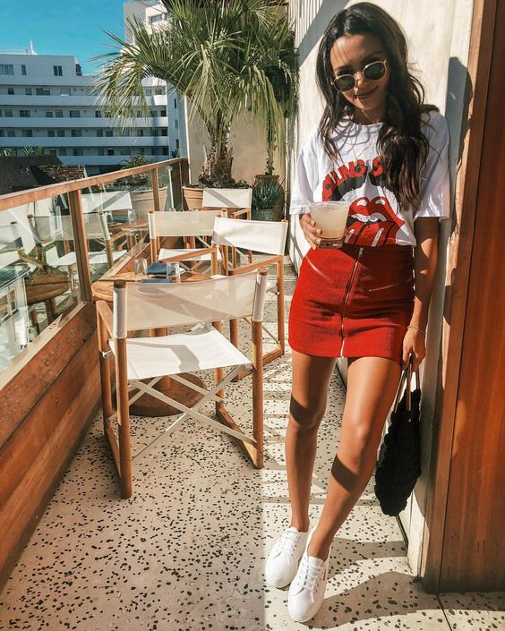 a graphic oversized tee, a red mini with a zip, white sneakers and a black bag