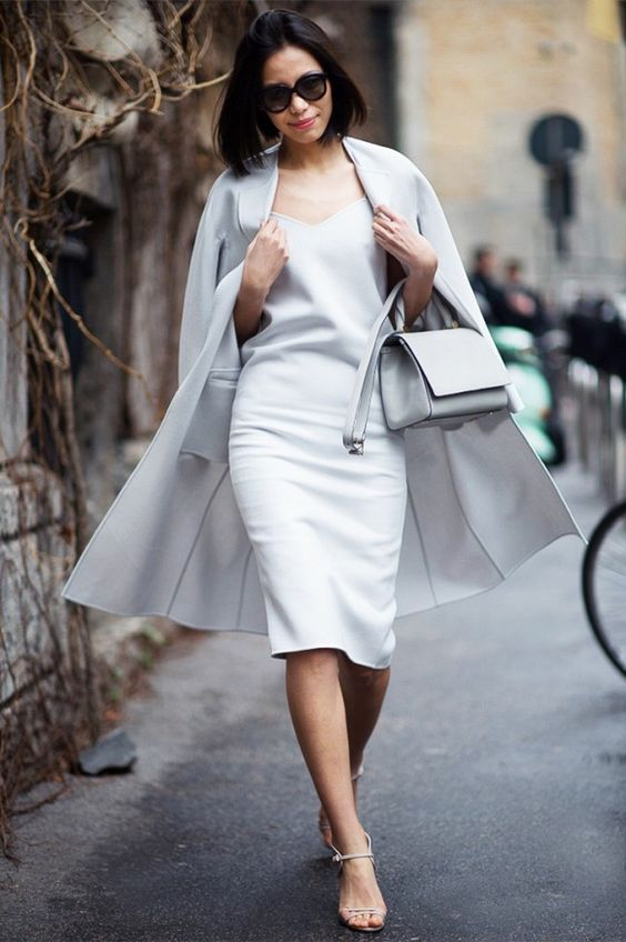a chic look with a white knee dress, a matching cape, white strappy shoes and a white bag