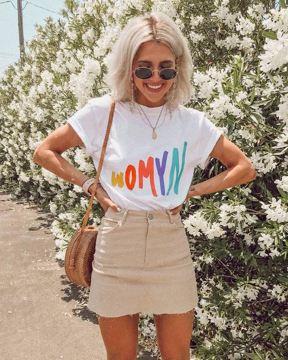 a graphic t-shirt, a tan denim mini skirt, a wicker round bag and round glasses for summer