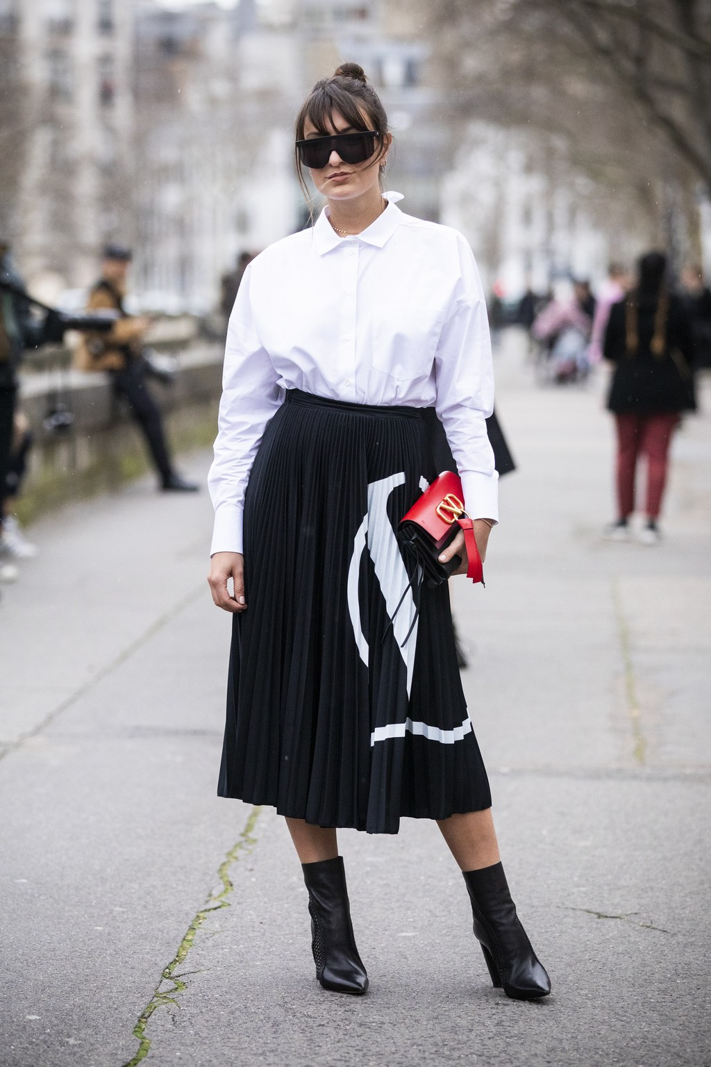 a white button down, a black and white patterned pleated midi, black boots and a catchy bag
