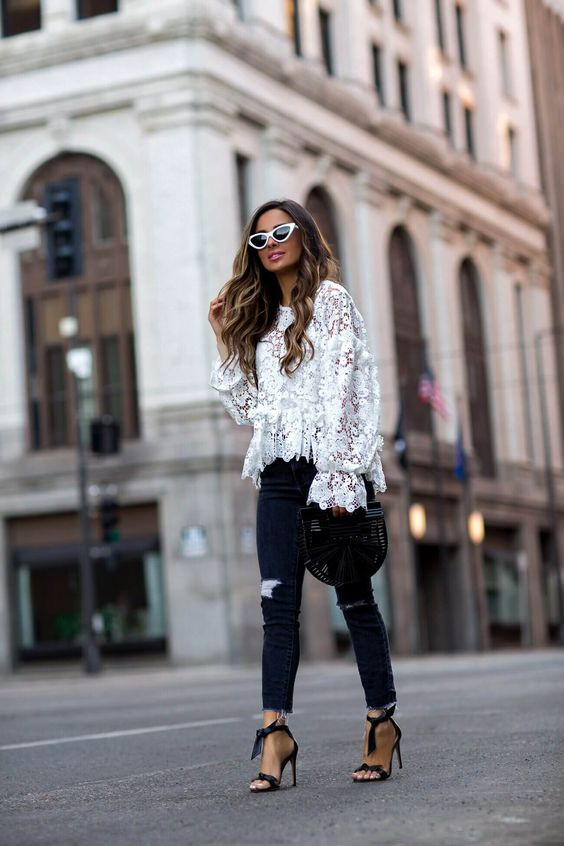 a white lace blouse with wide sleeves, black ripped skinnies, black ankle strap shoes and a black wooden bag