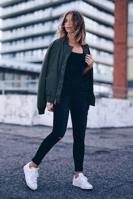 a black top, black ripped skinnies, white sneakers and a green bomber jacket
