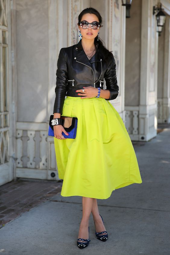 a cropped black leather jacket, a neon yellow midi A line skirt, quirky heels and a blue and black clutch