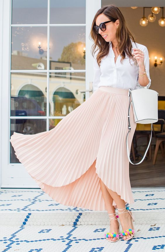 a white button down, a blush asymmetrical pleated midi, colorful pompom shoes and a bucket bag