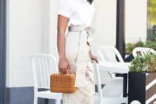 14 a white button down with short sleeves, a tan high waisted midi with a sash, white pumps and a wicker bag