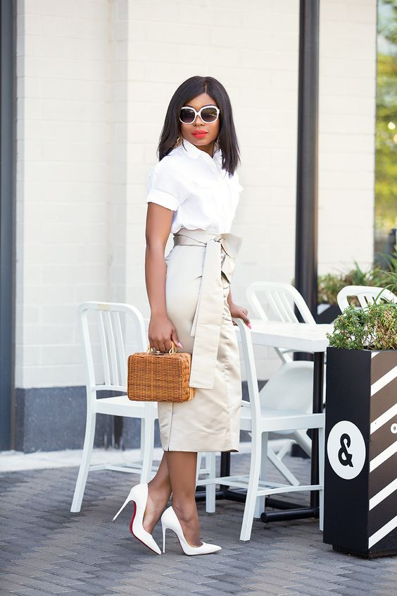 a white button down with short sleeves, a tan high waisted midi with a sash, white pumps and a wicker bag