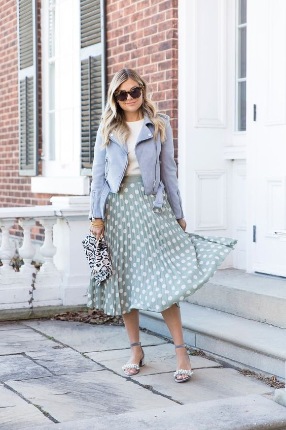 a white tee, a powder blue leather jacket, a green and white polka dot midi skirt, embellished heels and a printed clutch