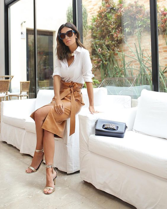 a white button down, a camel high waisted midi with a slit and a sash plus metallic heels