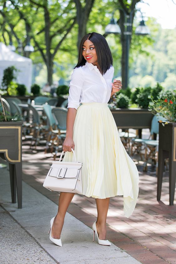 a white button down, a pale yelow asymmetrical pleated midi, white heels and a white bag