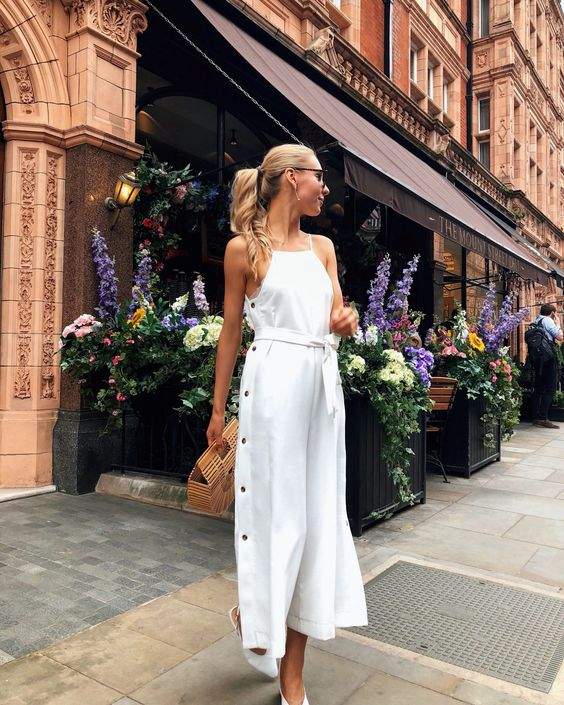 a white dress with a halter neckline, black buttons on the side, white slingbacks and a wooden bag