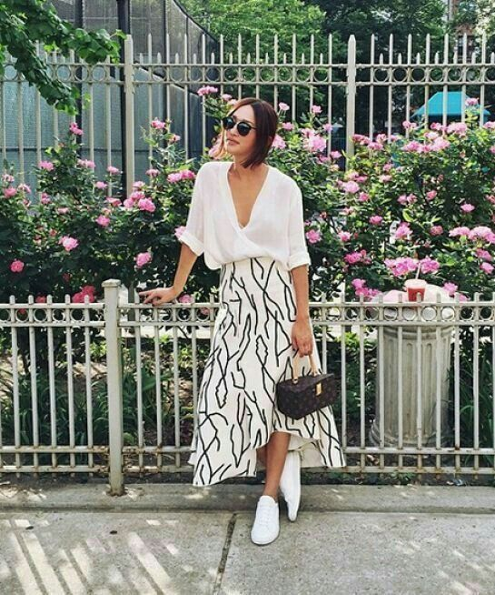 a white oversized button down, a printed asymmetrical midi skirt, white sneakers and a brown printed bag