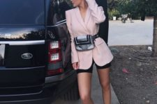 15 black bike shorts, a pink oversized blazer with a waist bag and metallic trainers