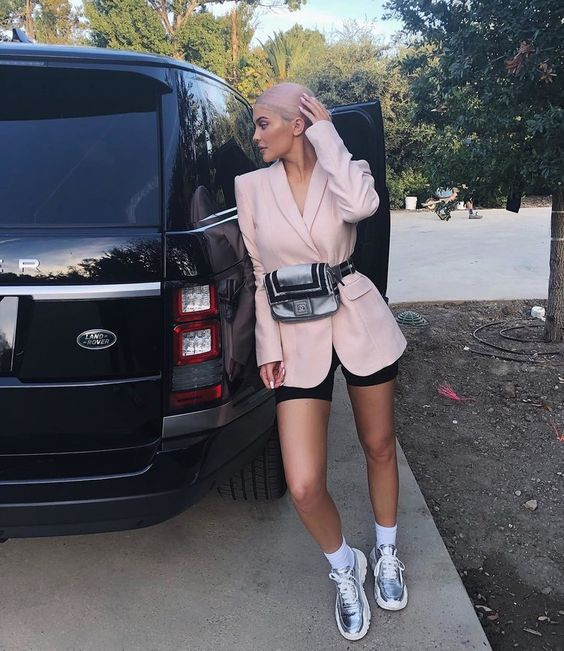black bike shorts, a pink oversized blazer with a waist bag and metallic trainers
