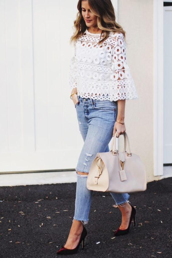 light blue ripped jeans, a white crochet blouse with bell sleeves and a high neckline, burgundy shoes and a neutral bag