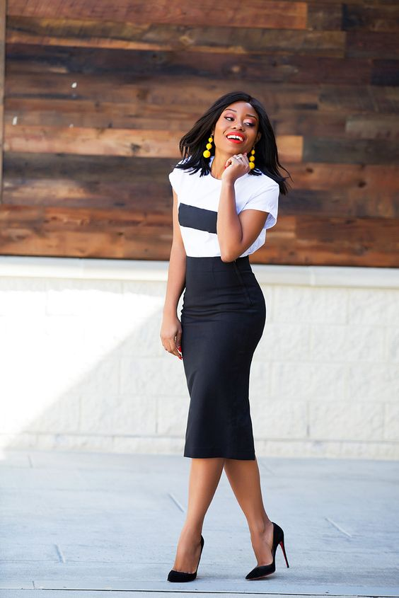 a white graphic tee, a black pencil midi skirt, black heels and statement earrings