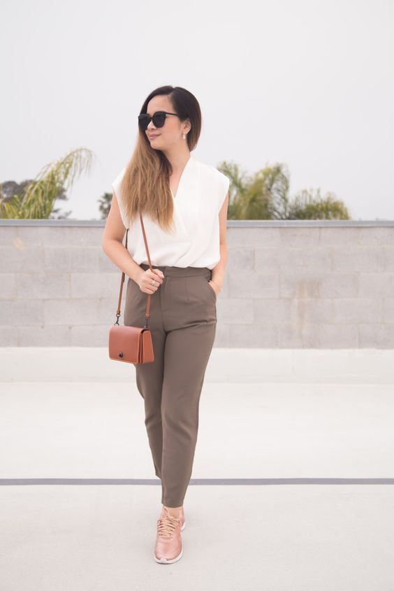 taupe pants, a white sleeveless top, blush sneakers and a camel bag for a summer work look