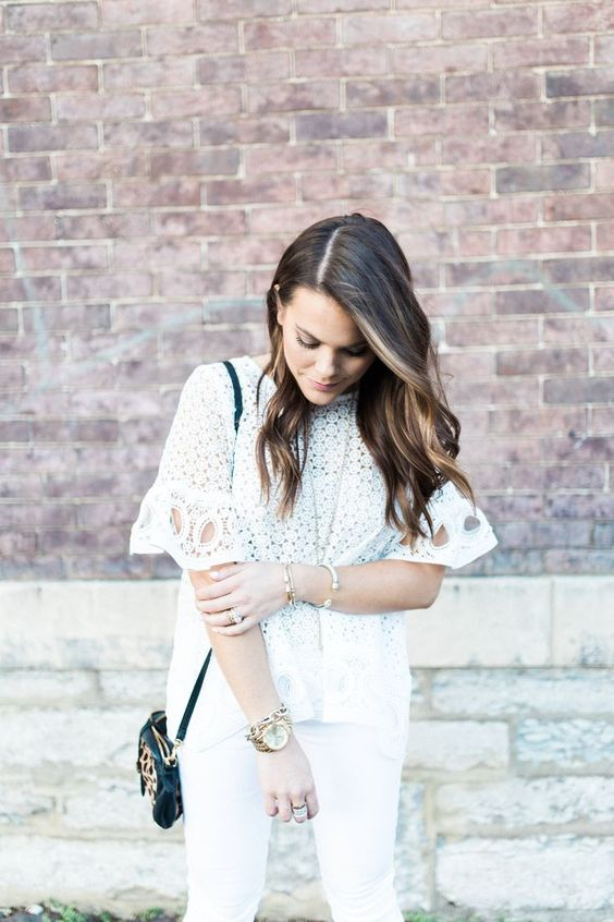 white skinnies, a white crochet lace blouse with short sleeves and a small black bag