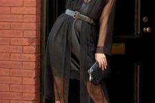 With black mini dress, belt, black clutch and cutout shoes
