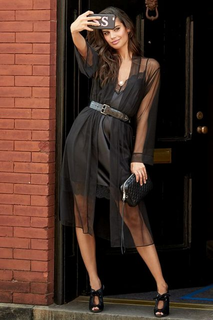With black mini dress, belt, black clutch and cutout shoes