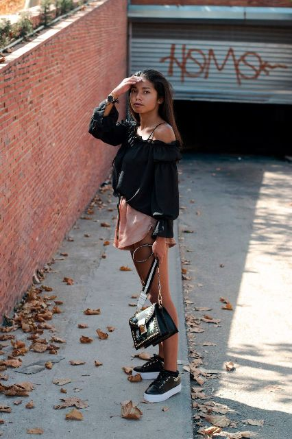 With black one shoulder blouse, black embellished bag and black and white sneakers