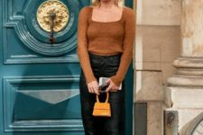 With black pants, yellow mini bag and beige shoes