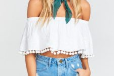 With distressed denim shorts and white framed sunglasses