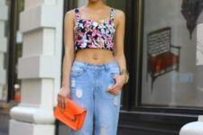 With distressed jeans, orange clutch and two colored shoes