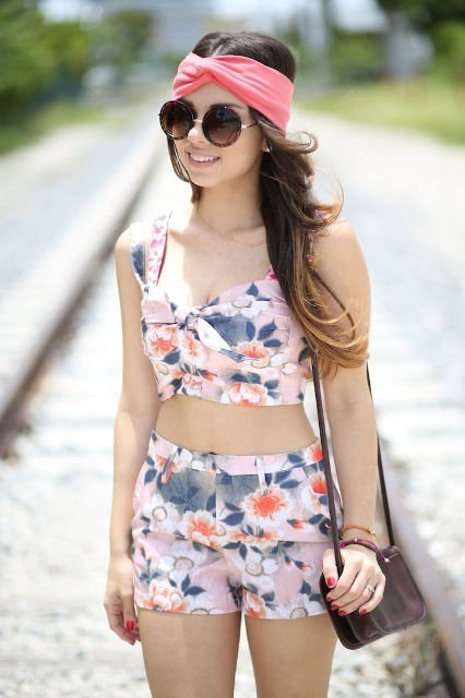 With floral shorts, rounded sunglasses and small bag