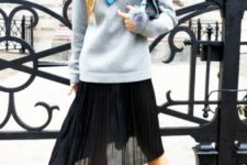 With light blue sweater, printed scarf, black clutch and black shoes