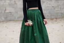 With necklace, embellished clutch and emerald maxi skirt