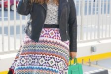 With printed shirt, black leather jacket, silver shoes and green bag