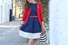 With white and blue dress, red cardigan, red shoes and printed tote