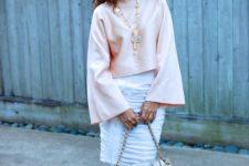 With white knee-length skirt, metallic bag and high heels