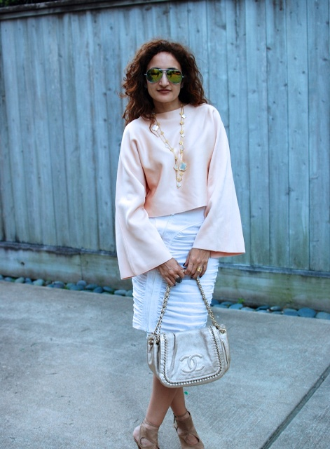 With white knee-length skirt, metallic bag and high heels